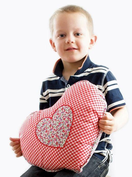 Kind mit herzförmigem Kissen